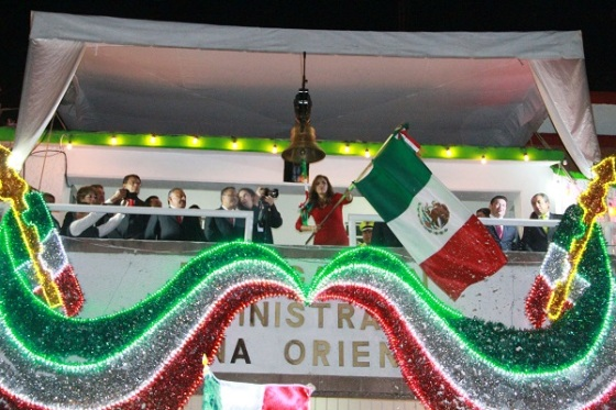 La presidenta municipal de Tultitlán, Sandra Méndez Hernández, ondea la bandera nacional desde el palacio municipal. Fotos: C. S.